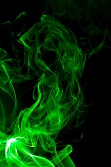 Fumée verte sur surface noire.