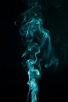Fumée verte tourbillonnante sur fond noir