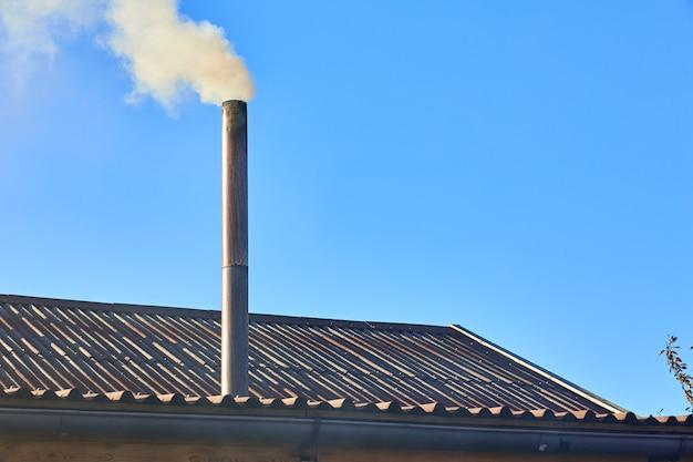 La fumée vient de la cheminée de la maison.