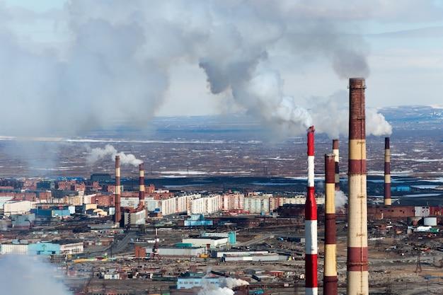Fumeurs de cheminées d'usine en arrière-plan de la ville.