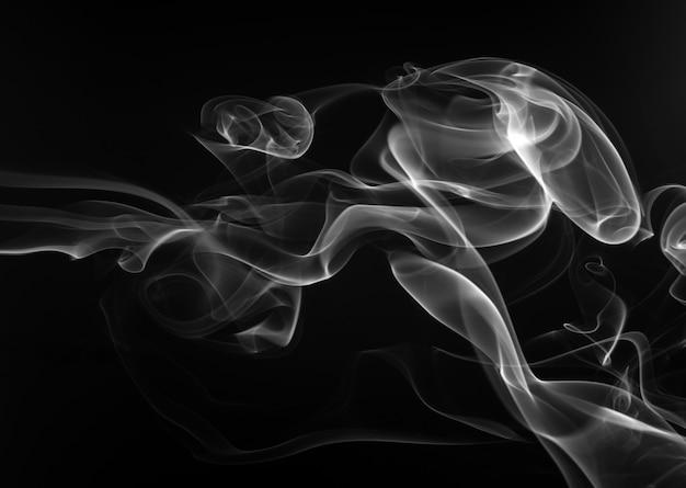Fumez l'encens blanc sur fond noir. concept d'obscurité
