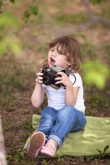 Fun kid fille réfléchie avec un appareil photo, pastel