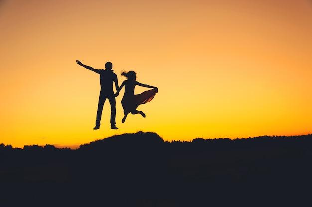 Fun loving couple sautant au coucher du soleil, silhouette