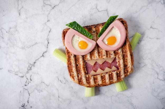 Fun sandwich monstre d'halloween avec saucisse de viande en tranches, œufs et fromage sur assiette