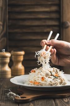 Funchoza de nouilles asiatiques avec du poulet et bâtons pour la nourriture sur le bois avec fond
