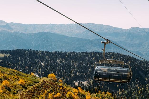 Funiculaire haut dans les montagnes au-dessus de la forêt d'automne