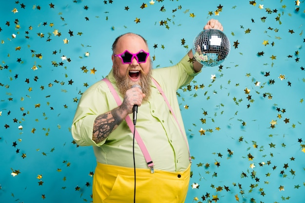 Funky guy hold disco ball chanter au micro sur fond bleu avec serpentine tombant