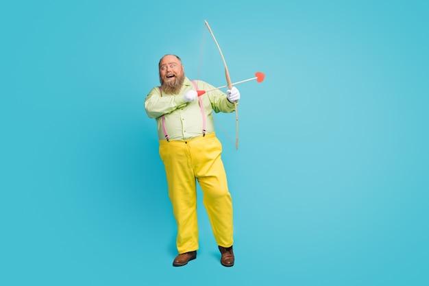 Funky homme en surpoids cupidon tirant des flèches dans l'espace vide de fond bleu