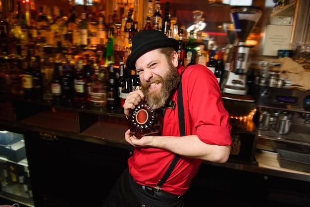 Funny camarade en chemise rouge détient une bouteille de whisky