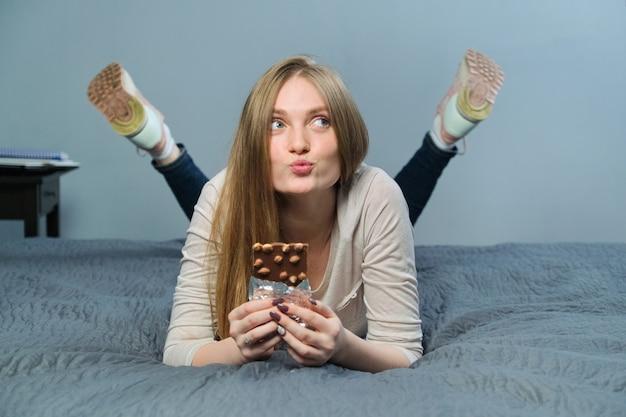 Funny émotionnelle girl holding chocolat au lait avec des noix entières dans sa main