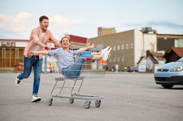 Funny family couple monte en chariot sur le parking