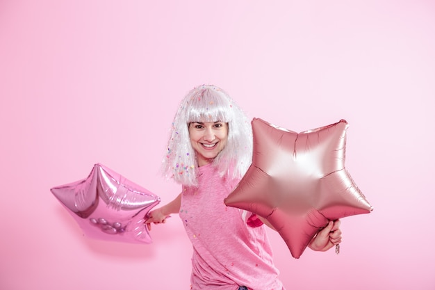Funny girl aux cheveux argentés donne un sourire et une émotion sur fond rose. jeune femme ou adolescente avec des ballons et des confettis