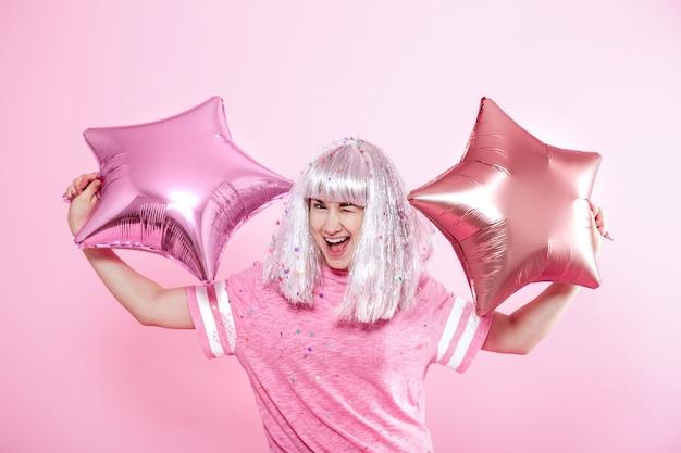 Funny girl aux cheveux argentés donne un sourire et une émotion sur le rose. jeune femme ou adolescente avec des ballons et des confettis