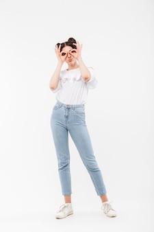 Funny girl gaie avec deux chignons coiffure vous regarde à travers des jumelles faisant avec les doigts, isolé sur blanc