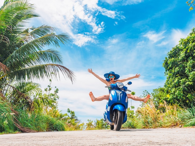 Funny girl avec les mains ouvertes sur une moto sur un fond de ciel bleu et vert tropiques