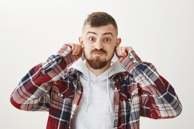 Funny guy ludique tirant les oreilles et faisant la moue, se moquant de quelqu'un