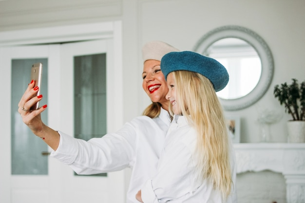 Funny happy fair hair long mom and cute girl making selfie together on mobile phone at lliving room, happy family lifestyle