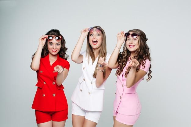 Funny ladies en costumes à la mode avec des shorts pointant à la caméra