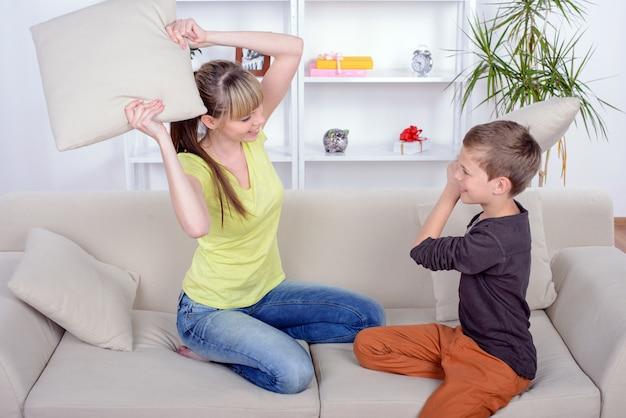 Funny mother and son se bat contre les coussins du canapé.