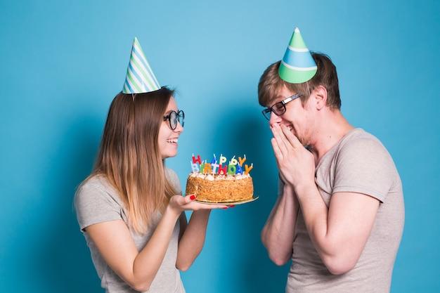 Funny nerd homme et femme portent des casquettes de vacances et des lunettes tenant un gâteau d'anniversaire avec des bougies