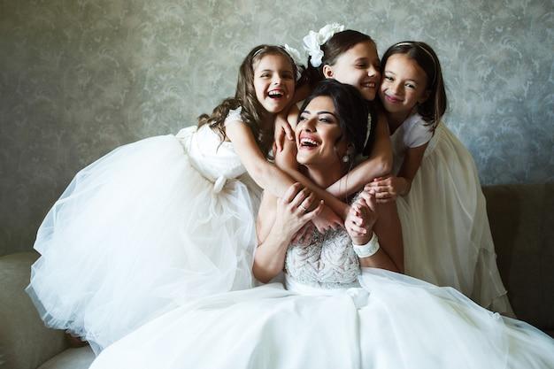 Funny petites filles en robes blanches se tiennent derrière la mariée assis sur le canapé