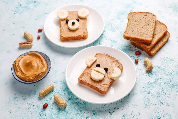 Funny sandwich à l'ours et au singe avec beurre d'arachide, banane et cassis, vue de dessus