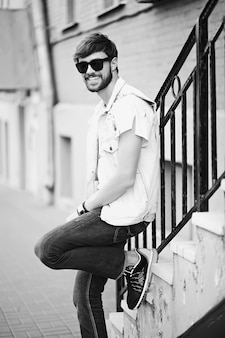 Funny smiling hipster bel homme beau en tissu d'été élégant dans la rue en lunettes de soleil