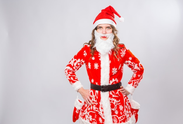 Funny woman in wearing xmas santa costume et barbe sur mur blanc