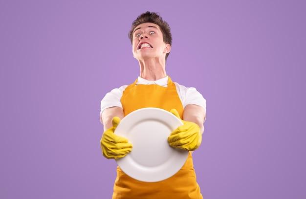 Furieux jeune homme en tablier jaune et gants tenant une plaque blanche claire tout en représentant la routine domestique