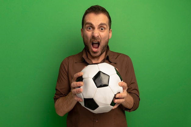 Furieux jeune homme tenant un ballon de football regardant à l'avant criant isolé sur mur vert