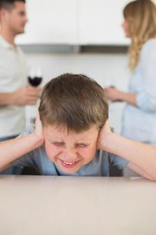 Furstrated garçon couvrant les oreilles pendant que les parents se disputent