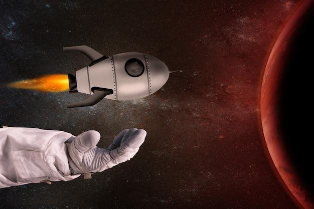 La fusée jouet dans les mains de l'astronaute en face de la planète rouge