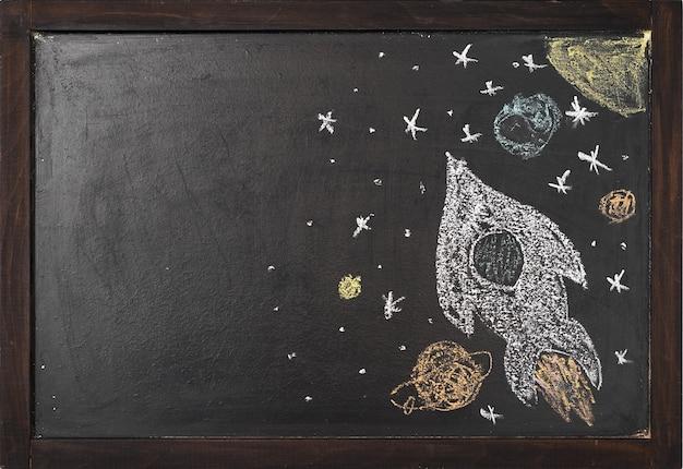 Une fusée avec des planètes est dessinée sur un tableau noir