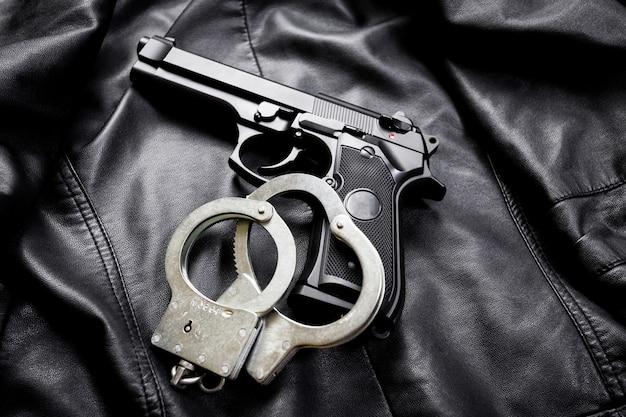 Fusil, arme à feu, couteau avec fourreau, boussole et cahier à stylo sur toile noire