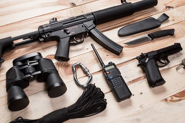 Fusil d'assaut, arme à feu, couteau avec fourreau, boussole et carnet avec un stylo sur la table.