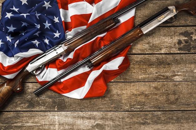 Fusil automatique sur le drapeau américain sur fond de bois