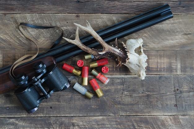 Fusil de chasse avec cartouches et crâne de cerf. vue de dessus.