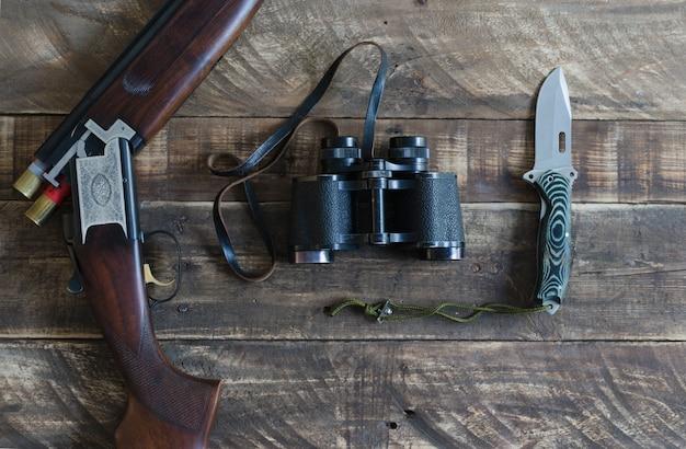 Fusil de chasse avec des jumelles et un couteau. vue de dessus.