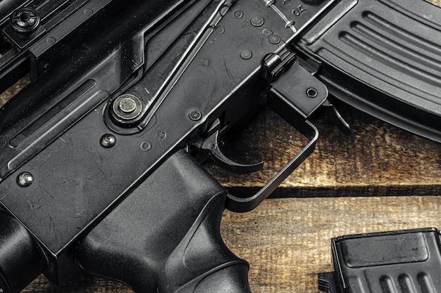 Fusil noir ak-47 sur planche de bois close up