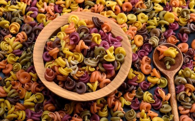 Fusilli de pâtes crues spirales multicolores dans un bol en bois