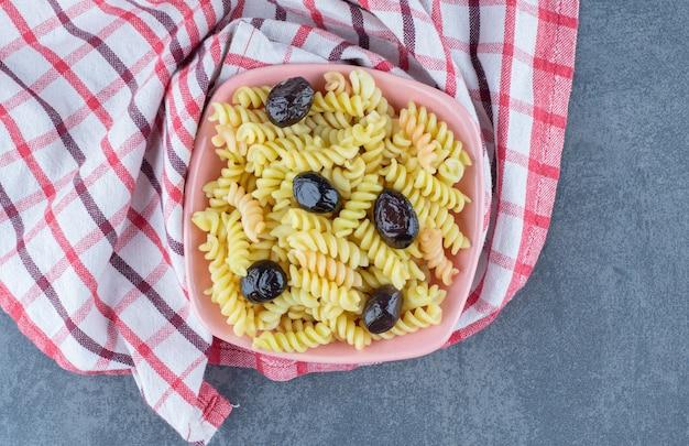 Fusilli savoureux aux olives dans un bol rose.