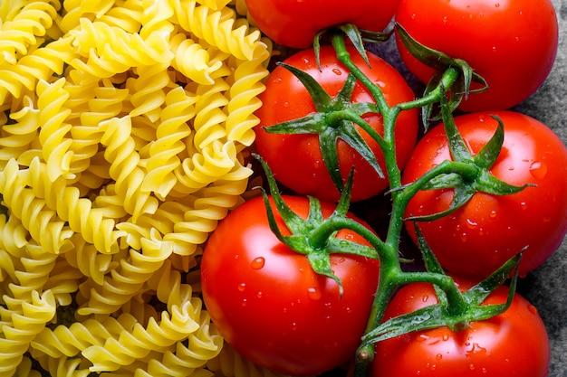Des fusilli séchés non cuits et des tomates fraîches se ferment. nourriture italienne. ingrédients pour la cuisson des pâtes