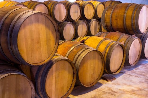 Fûts de chêne en bois de vin empilés dans une rangée à la cave