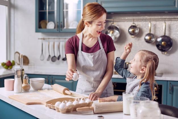 Futur boulanger. agréable petite fille portant un tablier et aidant sa mère à faire des biscuits tout en montrant un petit biscuit en forme d'étoile, l'ayant fait elle-même