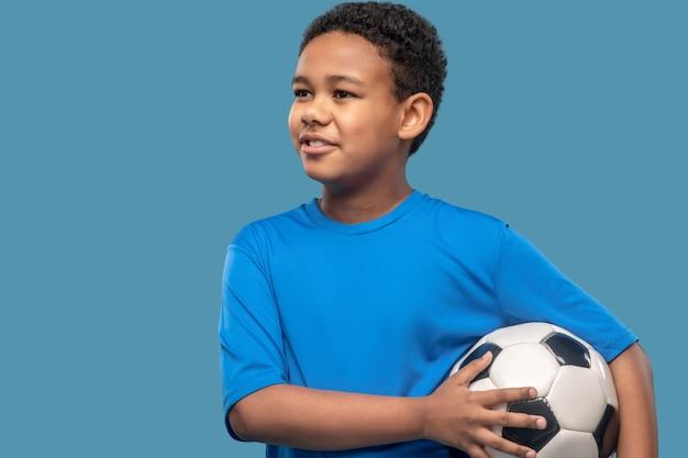 Futur footballeur. joyeux garçon à la peau foncée intéressé en chemise de sport bleue tenant un ballon de football debout en studio