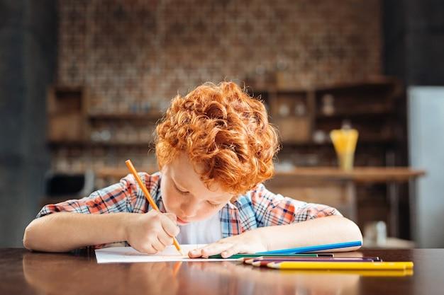 Futur grand artiste. adorable petit garçon assis à une table et se concentrant sur un morceau de papier tout en travaillant sur son prochain chef-d'œuvre à la maison.