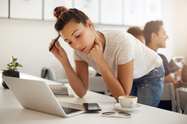 Futur graphiste confus travaillant sur son ordinateur portable dans un coworking ou un campus ensoleillé