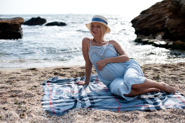 Future mère assise près de l'océan en robe et chapeau de style provençal bleu, rétroéclairage