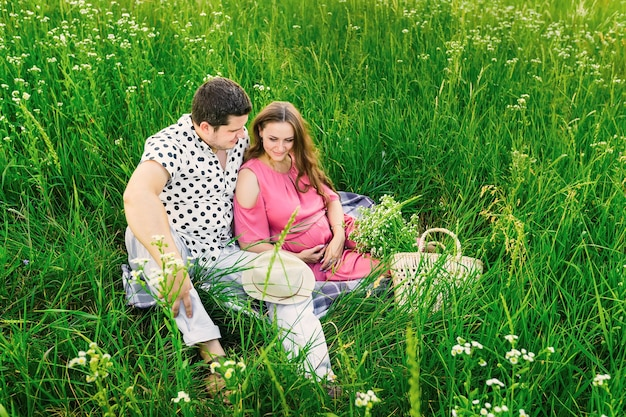 Futurs parents assis sur la couverture parmi les hautes herbes. sac avec un bouquet de fleurs et canotier.