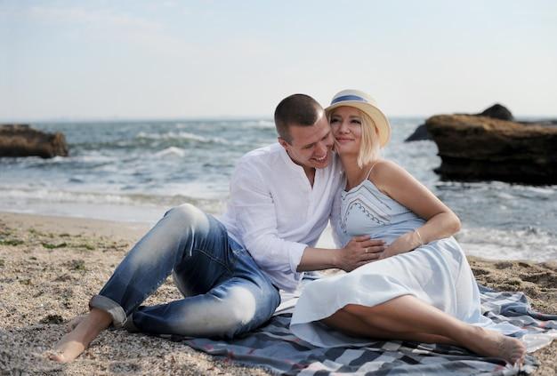 Les futurs parents heureux de jeune couple se reposent près de l'océan
